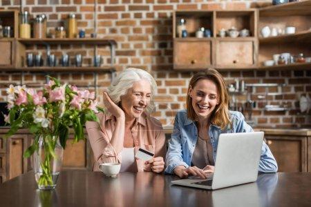 Photo pour Portrait de deux femmes, seniors et jeunes utilisant un ordinateur portable et une carte de crédit faisant des achats en ligne - image libre de droit