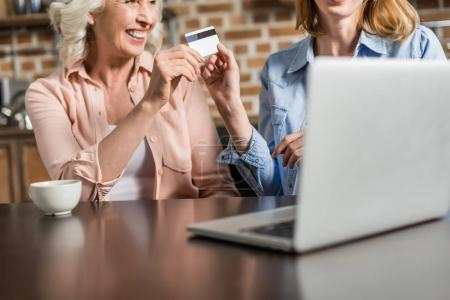 Photo pour Portrait de deux femmes, seniors et jeunes en utilisant l'ordinateur portable et carte de crédit, faire des achats en ligne - image libre de droit