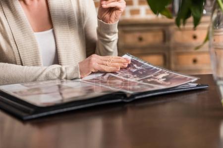 Photo pour Portrait de femme senior cheveux gris assis à la table de la cuisine et en regardant de gallerie de photos - image libre de droit
