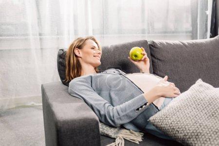 pregnant woman resting on gray sofa