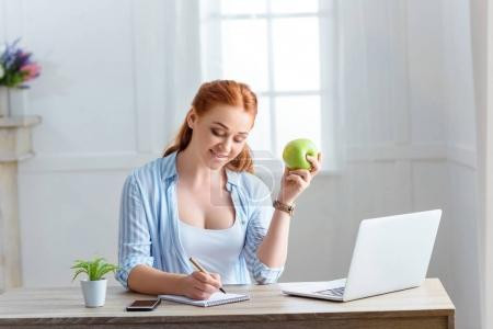 woman with apple writing in notepad