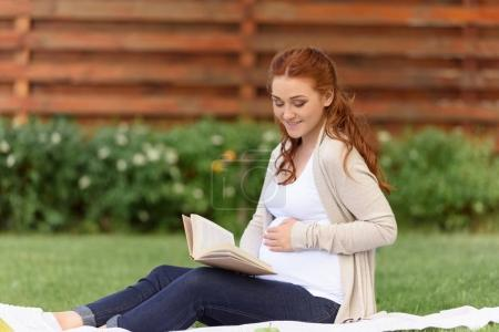 Photo for Happy beautiful pregnant woman reading book while sitting on green lawn - Royalty Free Image