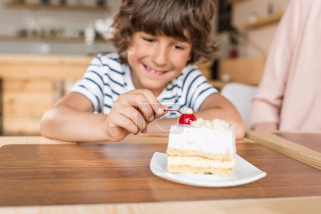 boy with piece of cake in cafe