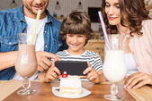 young family taking photo of dessert