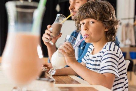 Photo pour Mignon petit fils et son père boire milkshakes dans café - image libre de droit