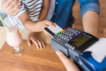 Photo pour Recadrée tir du père et fils, paiement par carte de crédit au café - image libre de droit