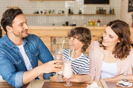 family drinking milkshakes in cafe