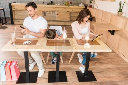 parents using gadgets while their son bored