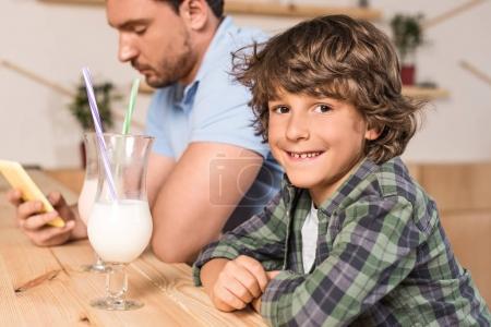 Foto de Lindo hijo sonriendo y a su padre beber batidos en la cafetería - Imagen libre de derechos