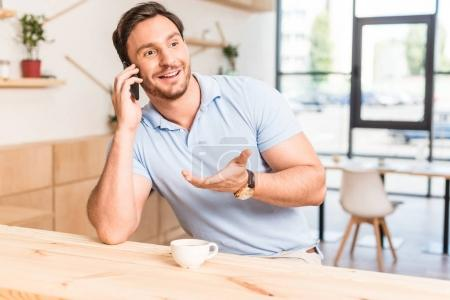 man talking by phone in cafe