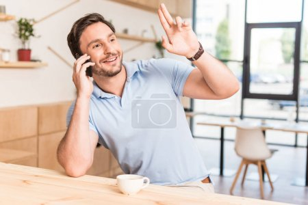 Man calling for waiter in restaurant