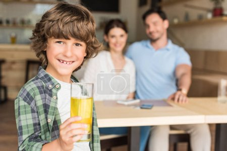 curly boy with glass of juice