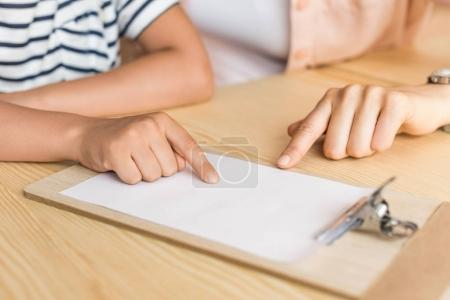 woman and boy pointing at blank paper