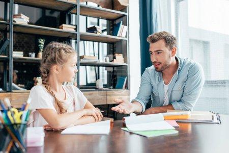 Photo pour Beau jeune père faisant ses devoirs avec sa petite fille - image libre de droit