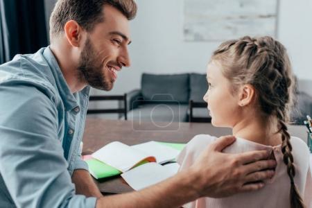 Photo pour Jeune beau père aider sa fille avec des devoirs - image libre de droit