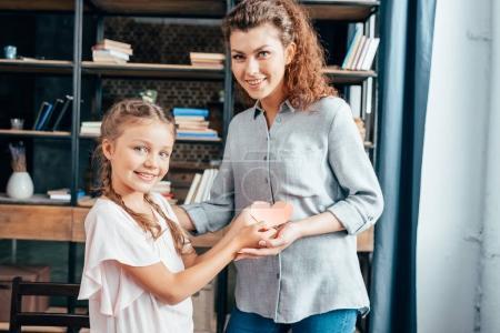 Photo pour Mère et fille tenant du papier sculpté en forme de coeur - image libre de droit