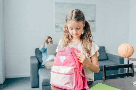 Photo for Cute little girl preparing backpack for school - Royalty Free Image