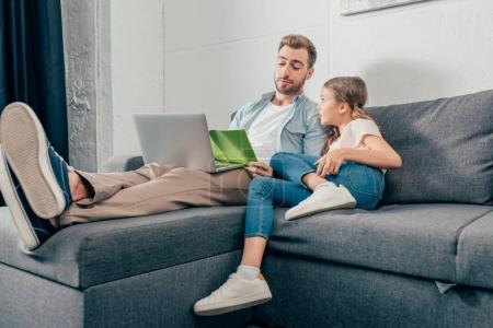 girl doing homework with father