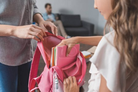 Photo for Cropped shot of mother and little daughter preparing backpack for school - Royalty Free Image