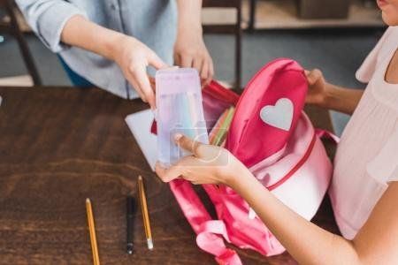 Photo for Cropped shot of mother and daughter packing stuff in backpack for school - Royalty Free Image