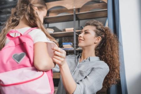 mother preparing daughter for school