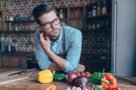Photo for Thoughtful handsome man at kitchen with various vegetables on table - Royalty Free Image