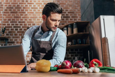 Photo for Thoughtful young man at kitchen with various vegetables on table - Royalty Free Image