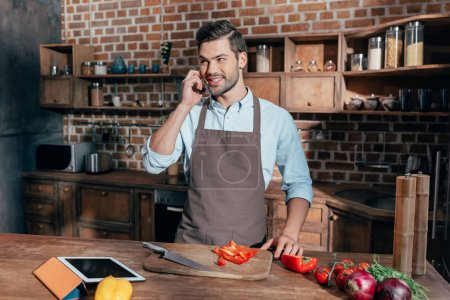 Photo for Handsome young man cooking and talking by phone - Royalty Free Image