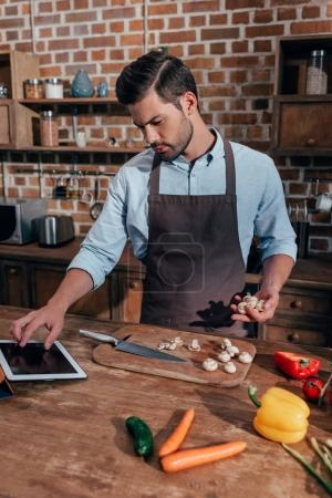 Photo for Stylish young man looking for recipe in tablet - Royalty Free Image
