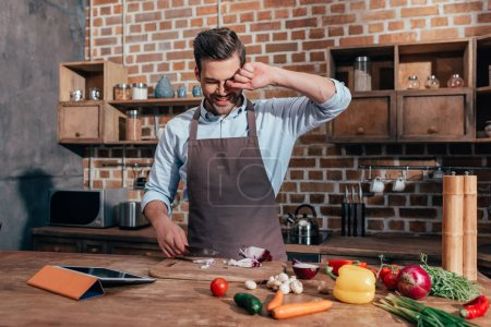 Photo for Handsome young man crying while cutting onion - Royalty Free Image