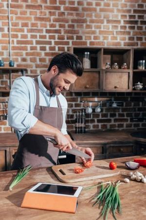 Photo pour Heureux jeune homme cuisine avec tablette - image libre de droit