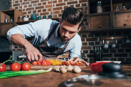 Photo for Concentrated young man with apron cutting vegetables - Royalty Free Image
