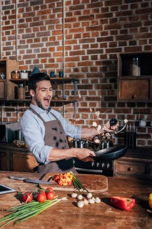 Photo pour Beau jeune homme avec tablier friture champignons - image libre de droit