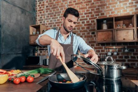 Photo for Pensive handsome man with apron cooking - Royalty Free Image