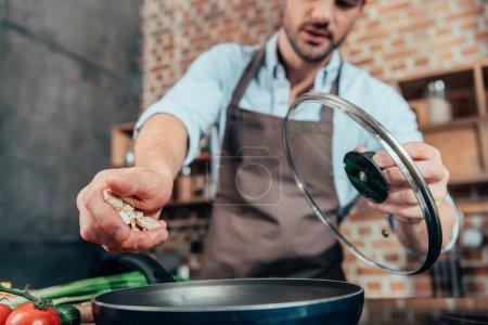 Photo pour Beau jeune homme ajoutant des champignons dans la poêle - image libre de droit