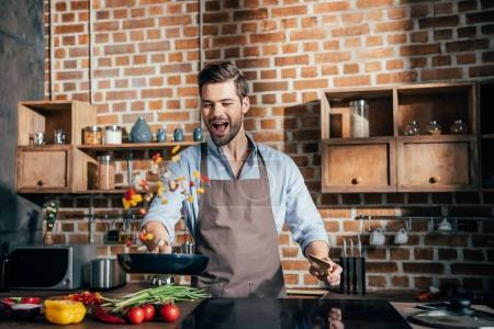 Photo for Stylish young man with apron frying vegetables - Royalty Free Image