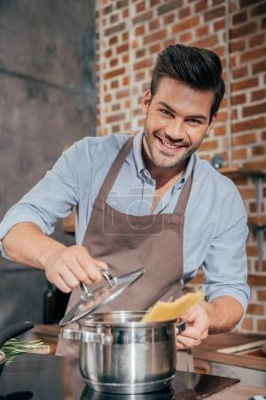 Photo for Handsome young man with apron cooking pasta - Royalty Free Image