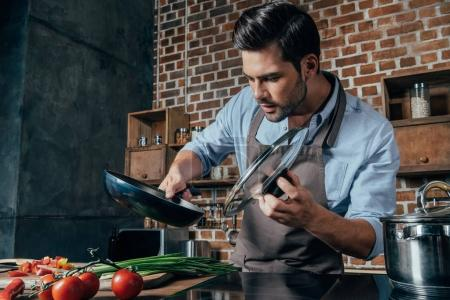 Photo for Handsome young man with apron cooking - Royalty Free Image