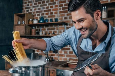 Photo pour Jeune homme souriant avec tablier cuisson pâtes - image libre de droit