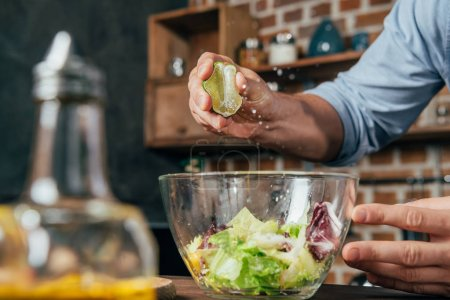 Photo for Man squeezing lime into salad - Royalty Free Image
