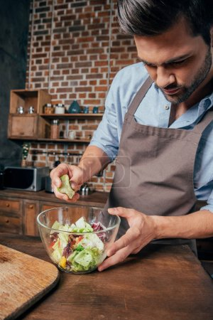 Photo for Passionated young man making salad - Royalty Free Image