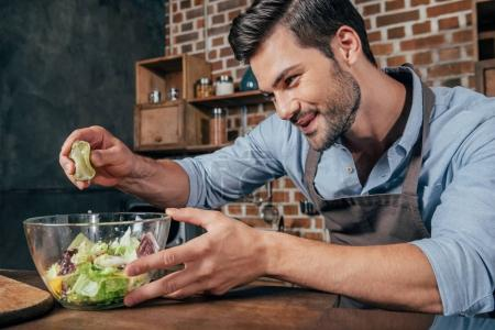 Photo for Excited young man making salad - Royalty Free Image