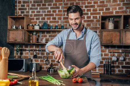 Photo for Handsome man in apron making salad - Royalty Free Image