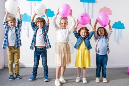 Photo for Adorable multiethnic kids holding balloons and smiling at camera at birthday party - Royalty Free Image