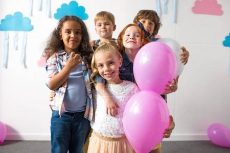 multiethnic kids with balloons at birthday party