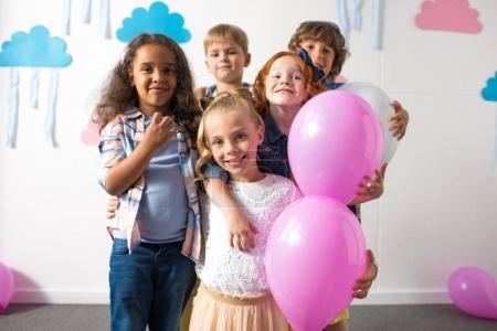 Photo pour Adorables enfants multiethniques tenant des ballons et souriant à la caméra à la fête d'anniversaire - image libre de droit