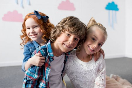 Photo for Portrait of adorable happy kids smiling at camera while embracing at birthday party - Royalty Free Image