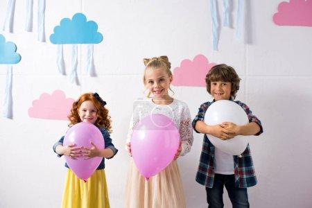 Foto de Adorables niños felices sosteniendo globos y sonriendo a cámara en fiesta de cumpleaños - Imagen libre de derechos