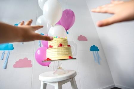Hands reaching to birthday cake