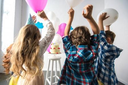 kids reaching to birthday cake
